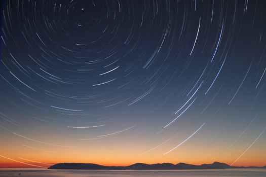 Cielo al atardecer con rayas blancas curvadas que representan movimientos representa